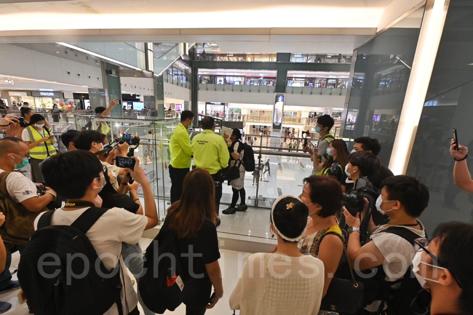 沙田新城市廣場保安要求市民保持距離和拿下標語。(宋碧龍/大紀元)