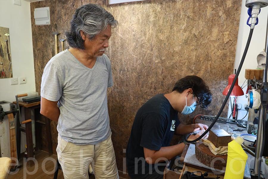 有逾50年打金經驗的黃師傅(左)教兒子Jason(右)傳統飾品製作工藝。(陳仲明/大紀元)