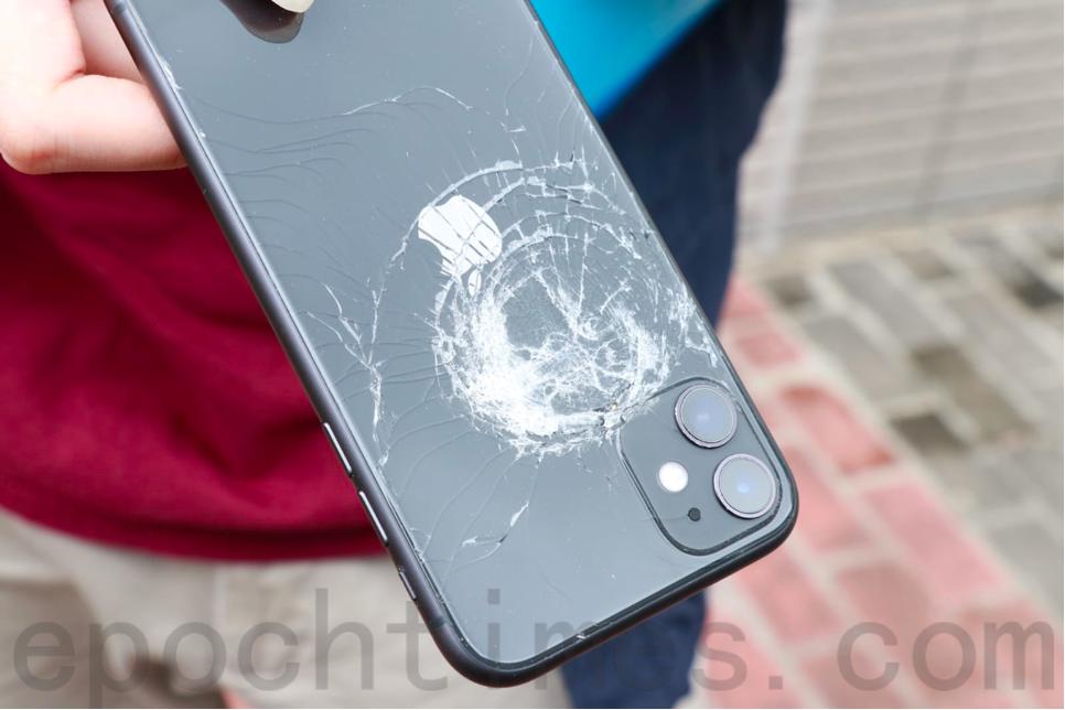 理大學生記者去年11月11日「黎明行動」期間在旺角以手機拍攝警方驅散人群,拍攝中的手機背面被防暴警員以胡椒球彈射中,明顯凹陷。(杜夫/大紀元)