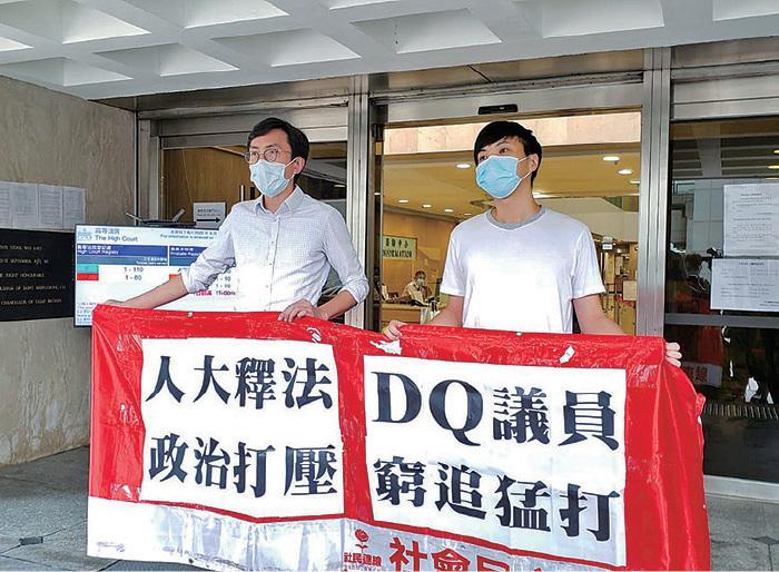 社民連秘書長吳文遠,就2016年「反釋法」遊行被判罪成提出上訴,他昨日進入法院前,與前嶺大學生會會長鄭沛倫拉起橫額。(郭威利/大紀元)
