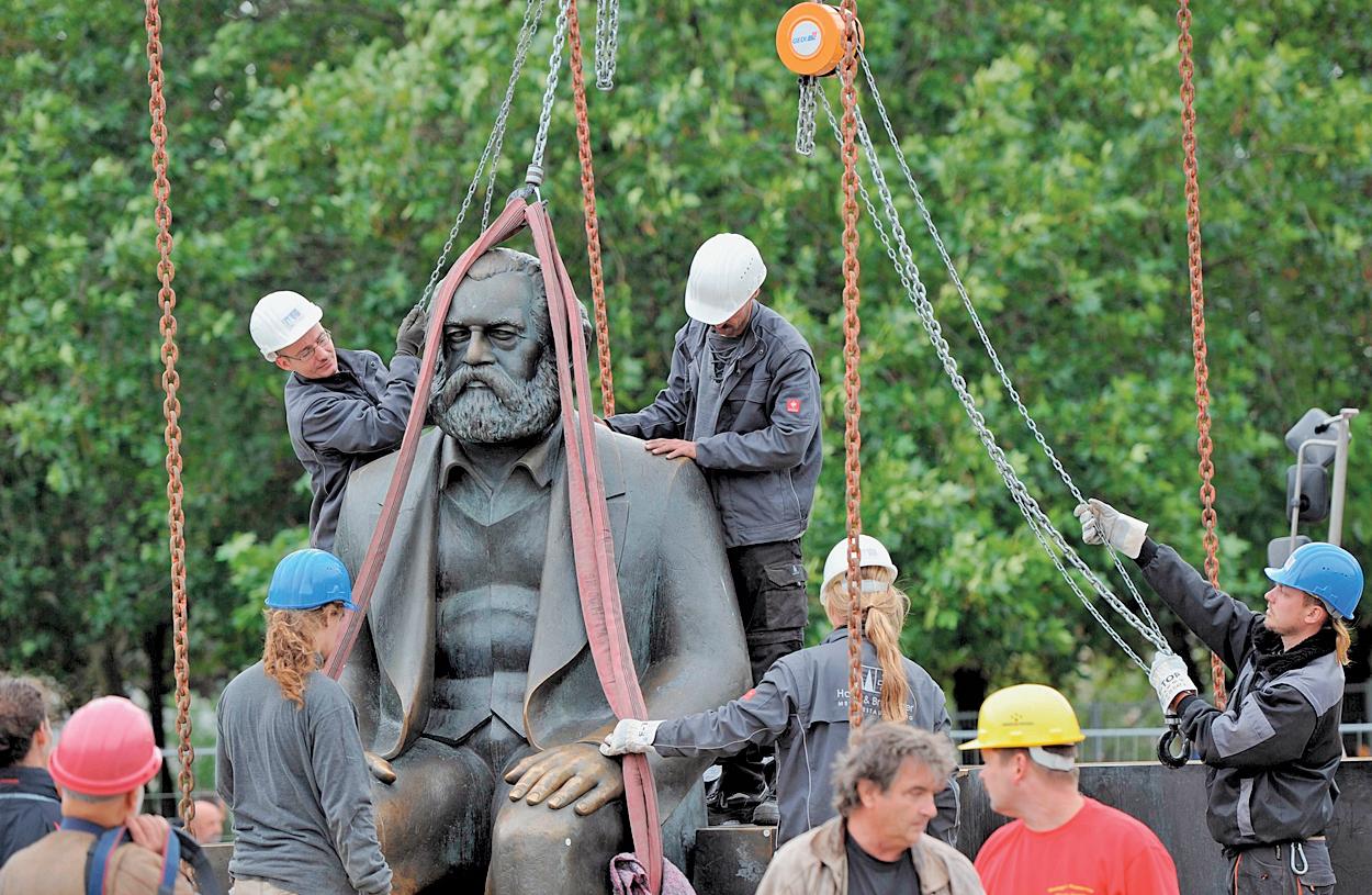 圖為2010年9月德國工人正在搬運柏林的一座馬克思雕像。雕像是1986年前東德共產黨頭目昂內克豎立的。(Getty Images)