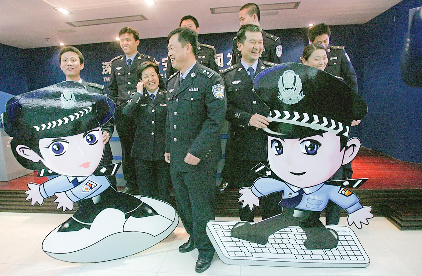 2007年1月26日,深圳一群中共網絡警察與一對名為「jingjing」和「chacha」的卡通網警合照。這對卡通網警自2006年起在深圳各大門戶網站巡邏,警示網民「自覺規範」網上行為。(Kirill Kudryavtsev/AFP/Getty Images)