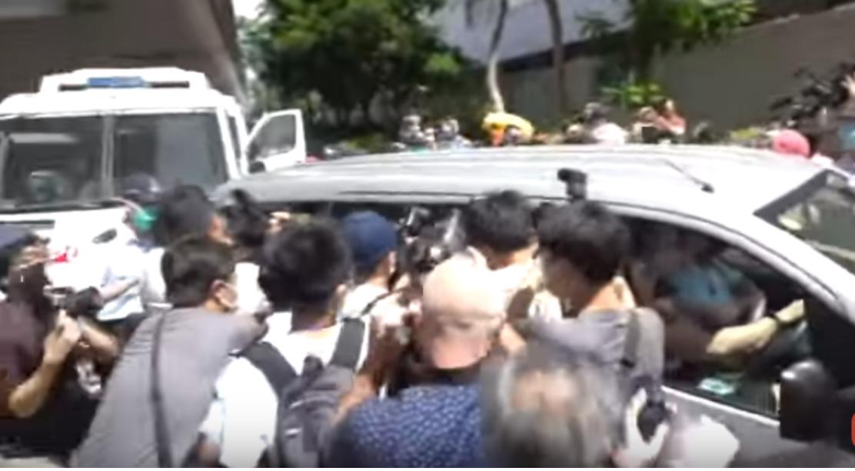 7月6日,載有本港首名「國安法」被告的車輛到達法院,大批記者擁上。(影片截圖)