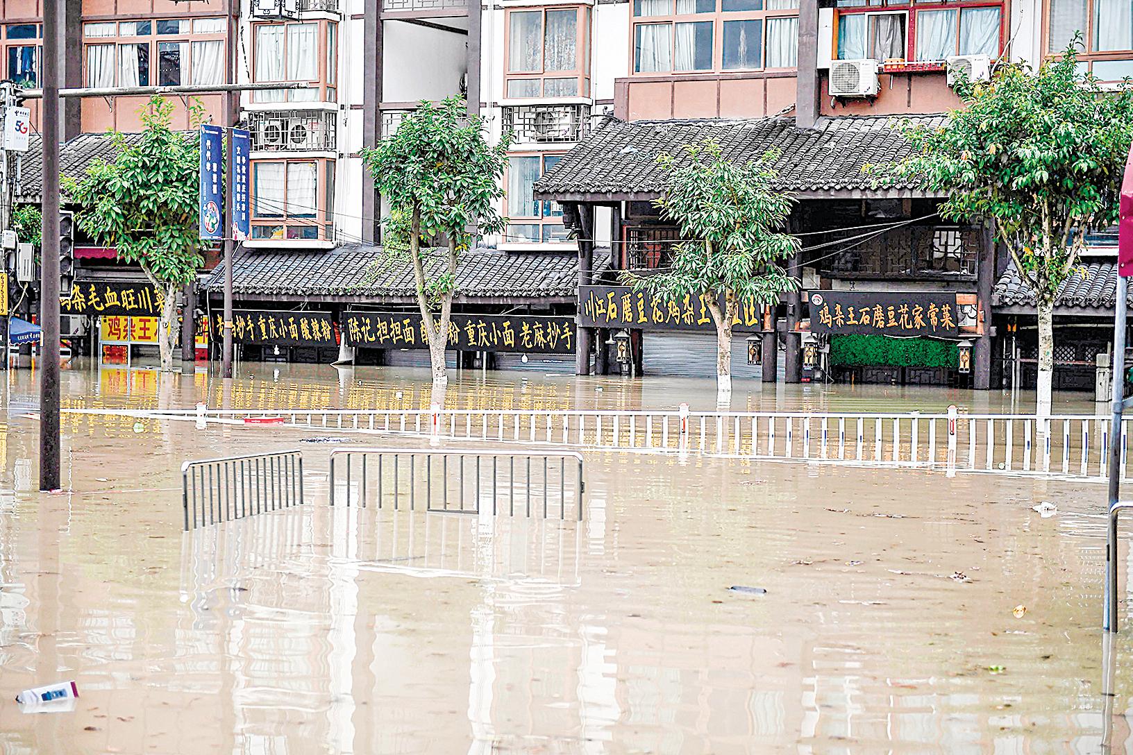 2020年8月19日,洪水漫入重慶,臨街商家被淹,僅剩招牌露出水面。(Photo by STR/AFP via Getty Images)