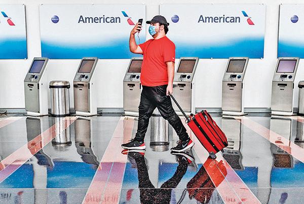 5月12日,羅納德 列根華盛頓國家機場,一名乘客經過空無一人的美國航空公司登記卡辦理處。(Getty Images)