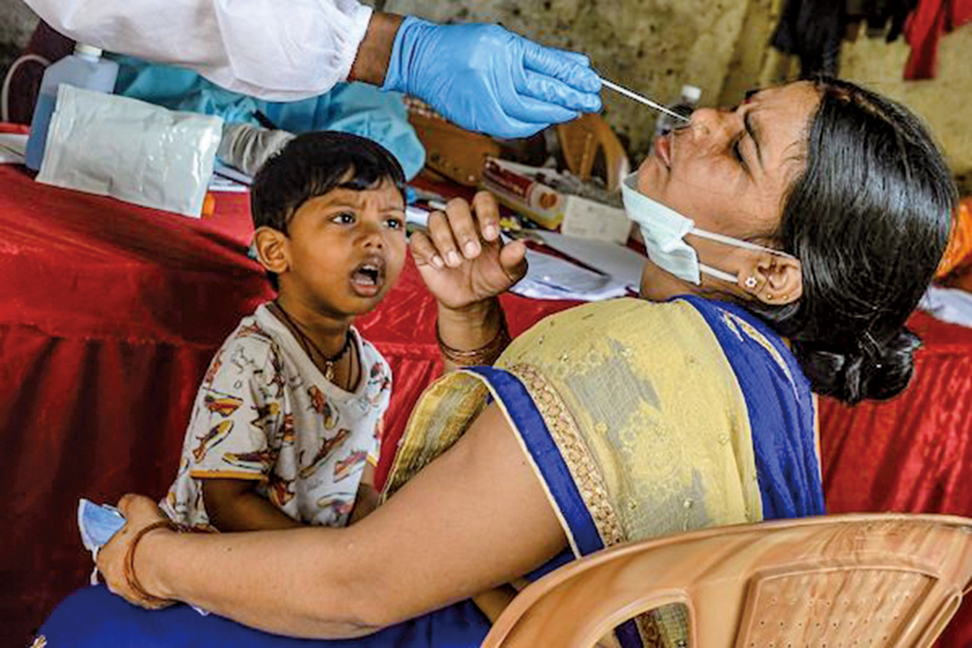 印度孟買一名醫務人員(左)從一位母親那裏收集鼻咽拭子。(AFP)