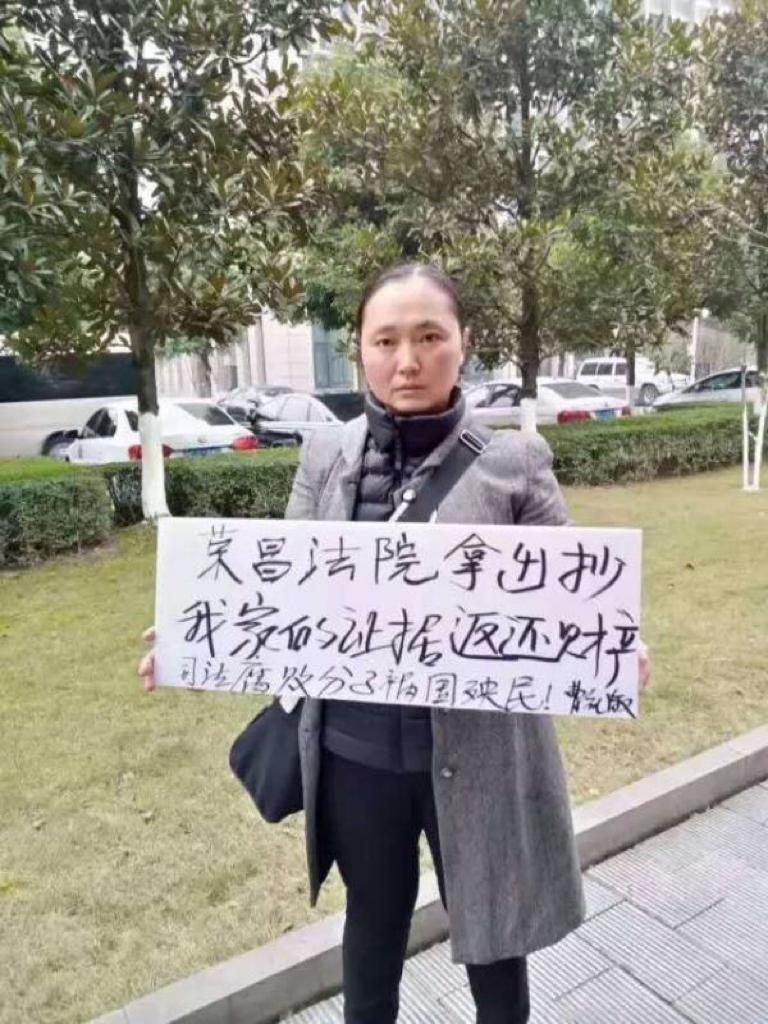 重慶曹女士打橫幅抗議當局強拆,要求歸還財產。(受訪者提供)