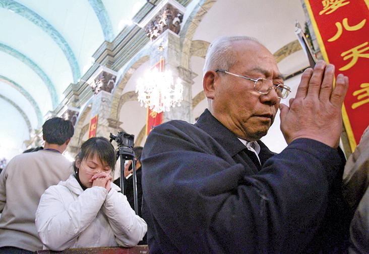 中共正在推行「無信仰證明」,作為在中共單位找工作的一個必要條件,有信仰人士的家屬也受到牽連。圖為北京民眾到教堂祈禱。(Getty Images)