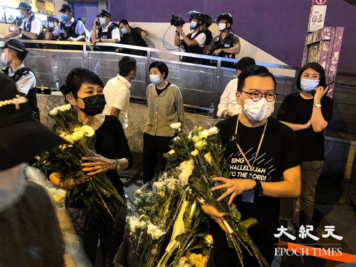 議員毛孟靜及何啟明在旁邊收集市民的獻花。(梁珍/大紀元)