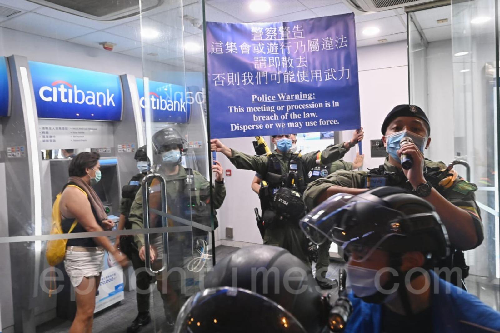警方舉起藍旗警告並驅趕現場記者。(宋碧龍/大紀元)