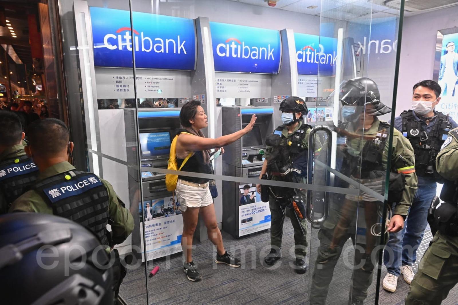 一名女士在太子站對面的花旗銀行裏被防暴警察截查。(宋碧龍/大紀元)