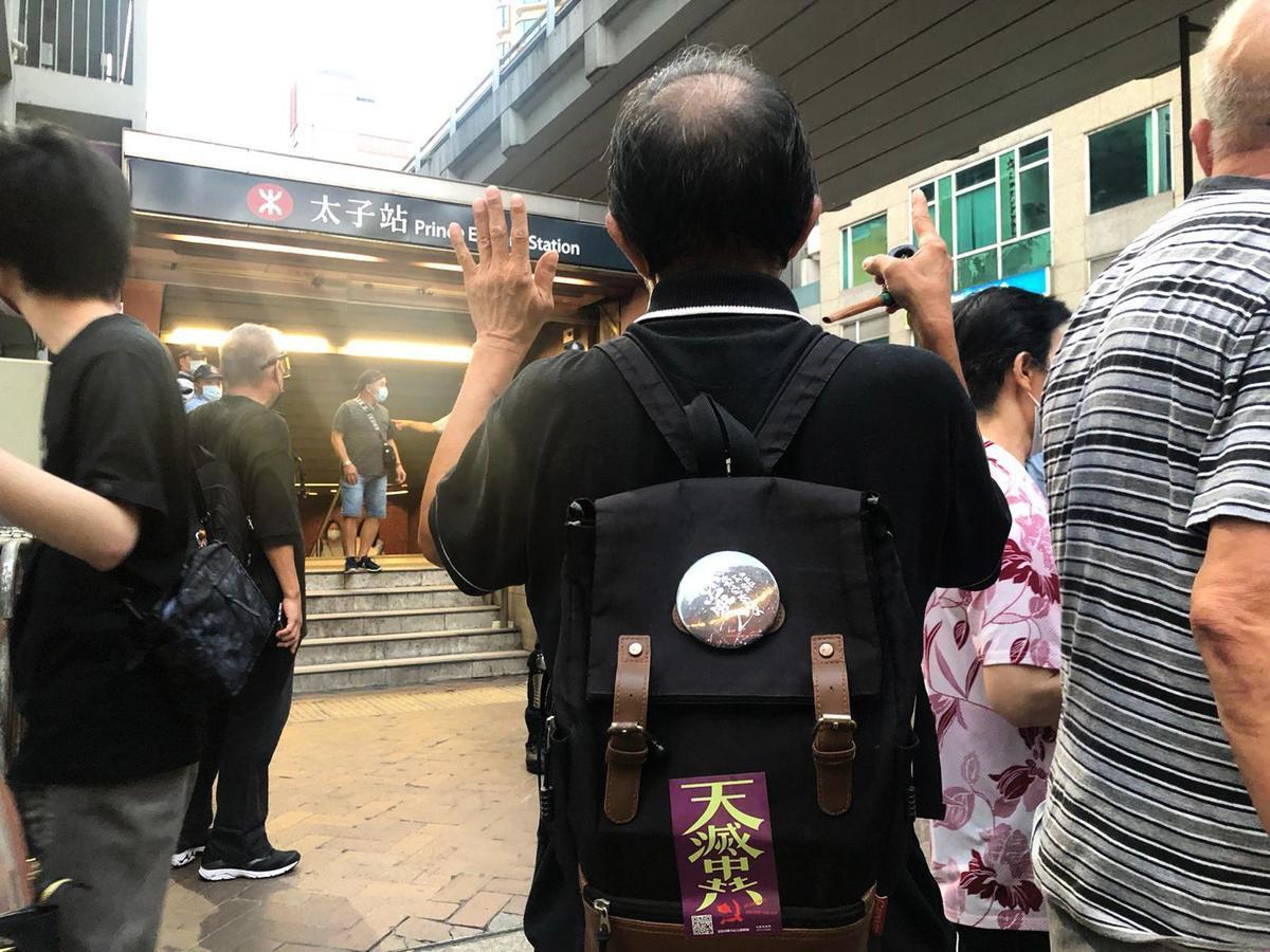 8月31日晚,前來紀念831襲擊事件一周年的黃先生展示背包上的「天滅中共」貼紙。他表示,相信真相即將大白於天下。(梁珍/大紀元)