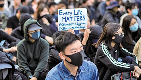 █ 去年12月22日,香港市民集會支持中國的維吾爾族人,隨後遭防暴警察暴力驅散,一名警察更一度舉槍指向一名高舉「天滅中共」海報的長者。 (ANTHONY WALLACE/AFP via Getty Images)