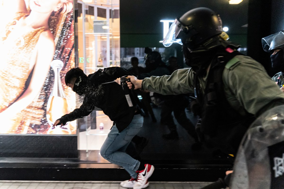 根據9月1日發佈的美國「2020年中國軍力報告」,中共曾在去年8月藉駐港部隊輪換,增派武警入港鎮壓抗議民眾。圖為去年12月28日,香港一名防暴警察向一名抗議者射擊胡椒噴霧劑。(Anthony Kwan/Getty Images)