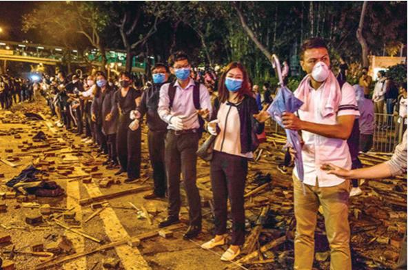 2019年11月18日晚,大批聲援被困理大生的市民,在校園一帶主要馬路與防暴警對峙,並組成人鏈運送物資。(AFP)