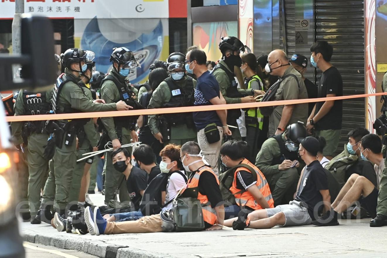 防暴警察封鎖旺角山東街和西洋菜南街 ,現場被捕人士成一排坐地上。(宋碧龍/大紀元)
