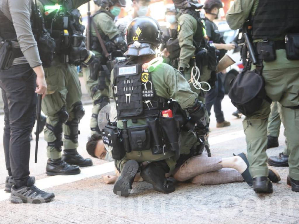 全副武裝的防暴警察於彌敦道及豉油街交界處拘捕了數名男子,一名男子遭到警方的跪壓。(余剛 / 大紀元)