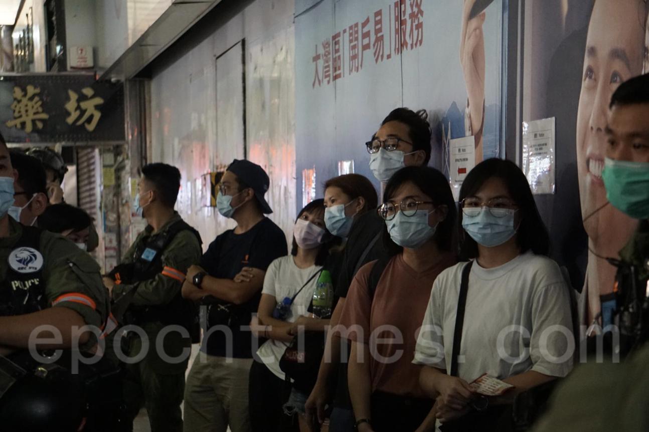 還有六名市民未能夠上車,在豉油街中國銀行外由警方自守等待車輛。(Jerry/大紀元)