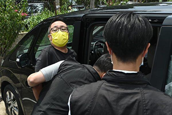 9月6日,香港民主派政黨「人民力量」副主席譚得志(戴黃色口罩者),被多名便衣警察撬門闖入後拘捕。(宋碧龍/大紀元)
