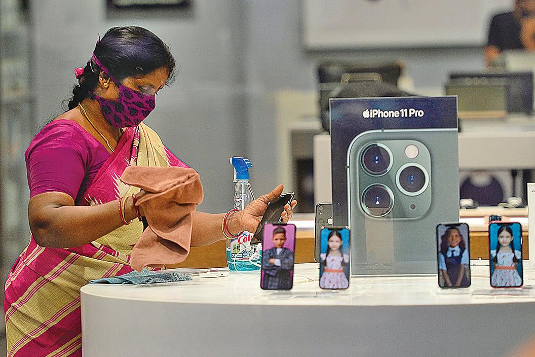 圖為印度清奈一名正在消毒的蘋果商店店員。(AFP)