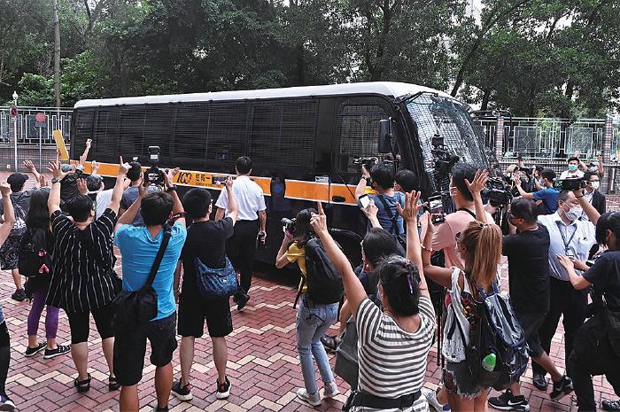 接載譚得志的囚車駛離法院,大批市民高叫口號,並舉起代表「五大訴求 缺一不可」的手勢。(宋碧龍/大紀元)