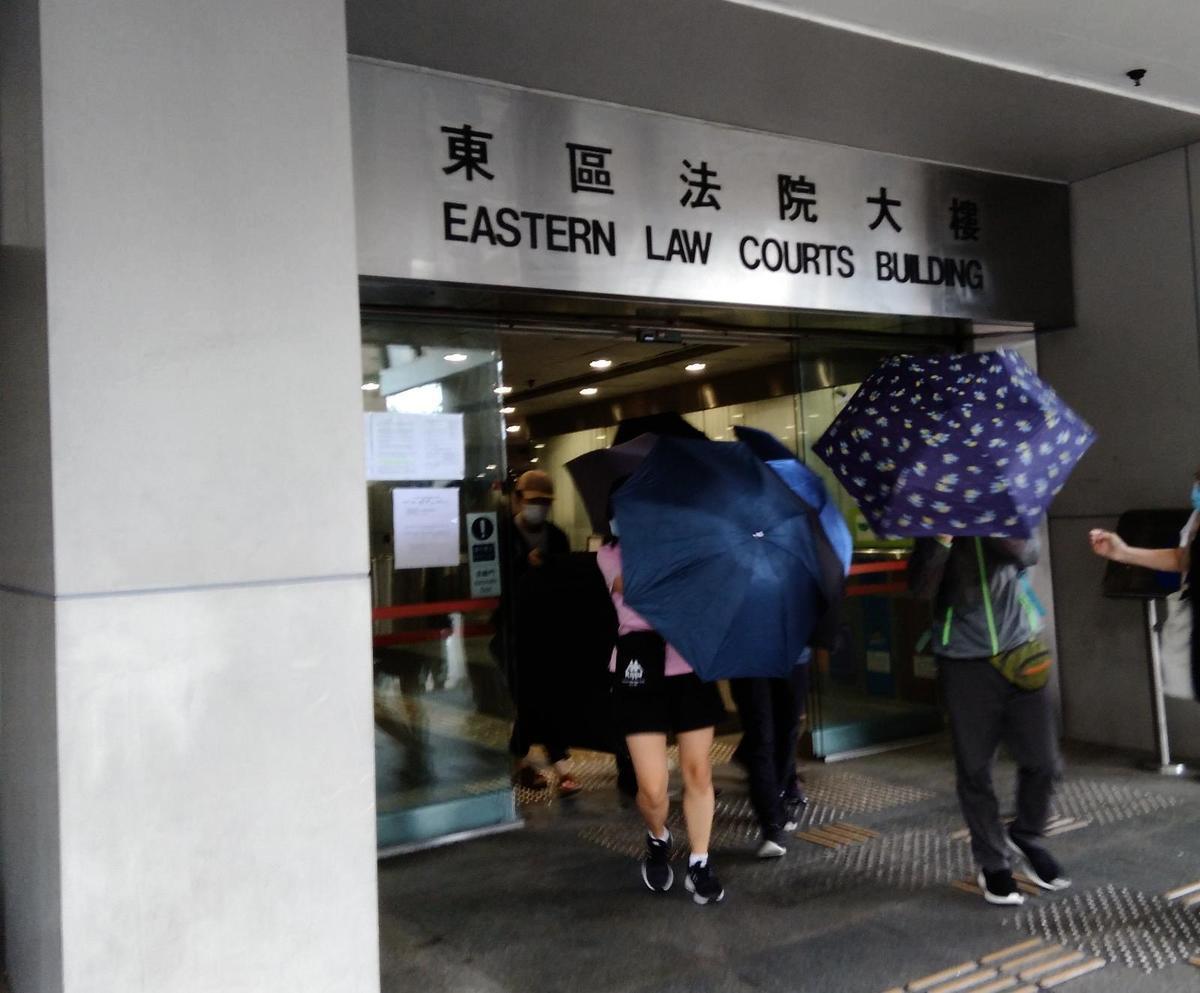 17歲被告被控兩罪於東區裁判法院審理。熱心旁聽市民打開傘陣抵擋記者鏡頭,以免被告被攝,遭受惡意起底針對。(杜夫/大紀元)