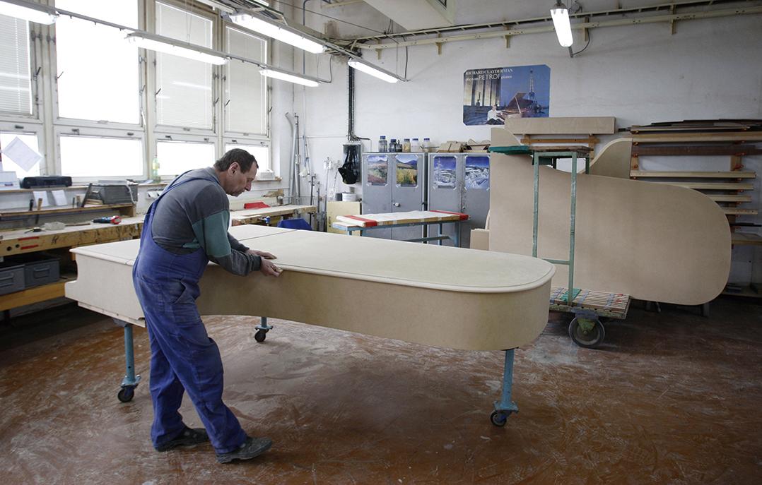 圖為2009年2月捷克知名鋼琴製造商佩卓夫(Petrof)的工廠內,員工正在組裝鋼琴。(Milan Jaros/AFP)
