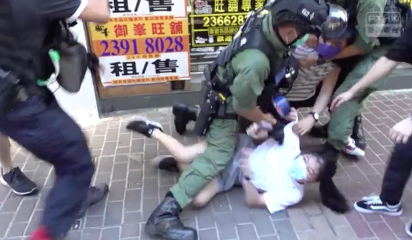 9.6九龍大遊行中,警方用膝蓋壓倒一名12歲女童的強力執法行為備受爭議。(港台影片截圖)