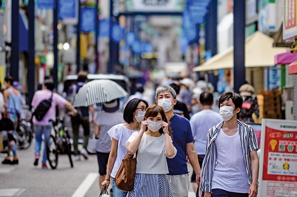 圖為8月1日,日本東京,街上的民眾戴著口罩。(AFP)