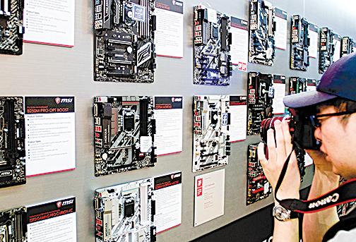 2017 年 5 月 30 日,台北年度電腦和技術展覽上,一位訪客正在拍攝主板壁的照片。(SAM YEH/AFP via Getty Images)