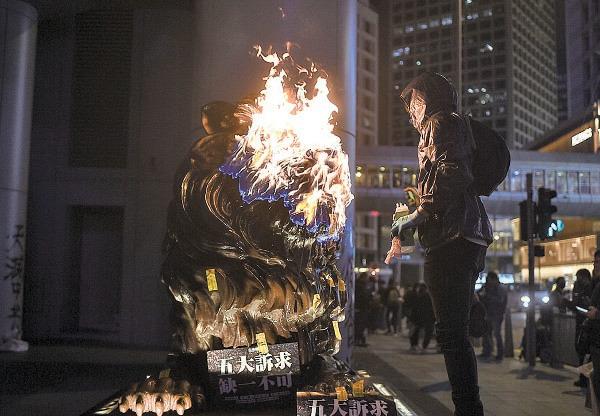 滙豐去年12月關閉支援本港反送中抗爭者的民間組織「星火同盟」的銀行賬戶,引發市民不滿。圖為今年1月1日,滙豐總行前獅子被放火。(PHILIP FONG/AFP via Getty Images)