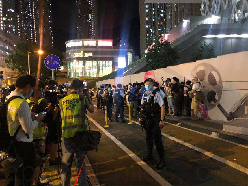 今晚(9月22日)有市民在知專設計學院悼念陳彥霖逝世周年,警方用橙色封鎖線包圍記者,檢查記者證件。(梁珍/大紀元)