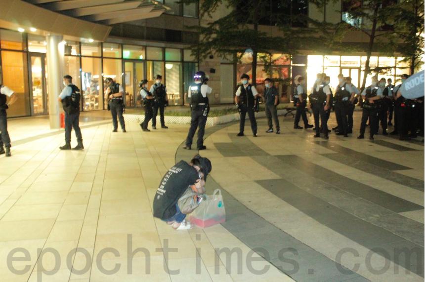 一名女士被警員截查後,坐在警方防線前哭泣。(Chris/大紀元)