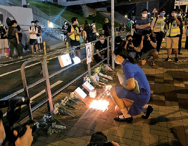 數十名市民晚上在陳彥霖身前就讀的知專設計學院外悼念,有中六學生身穿校服到場獻花。(梁珍/大紀元)