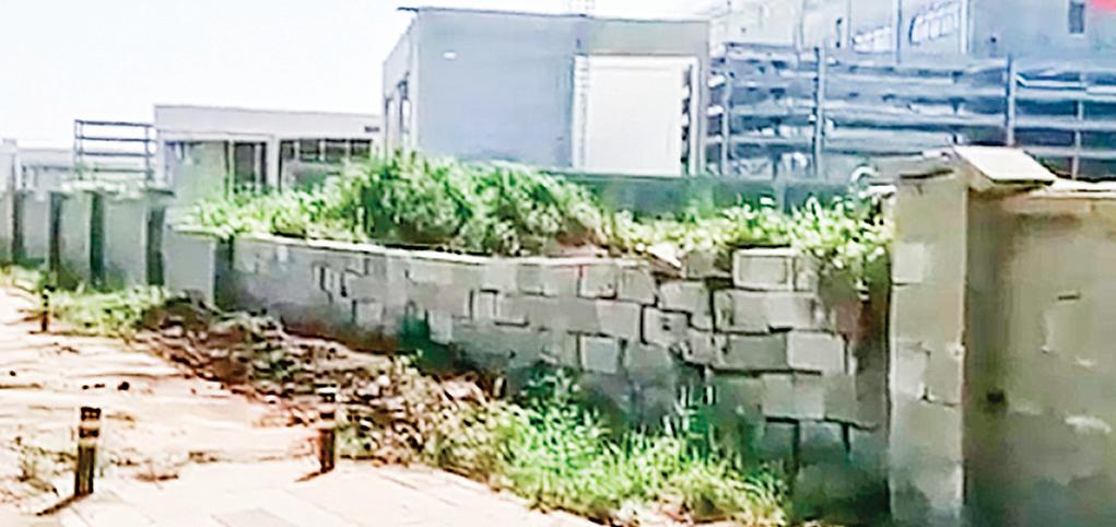 武漢弘芯停工後的建築工地雜草叢生,圍牆簡陋。(影片截圖)