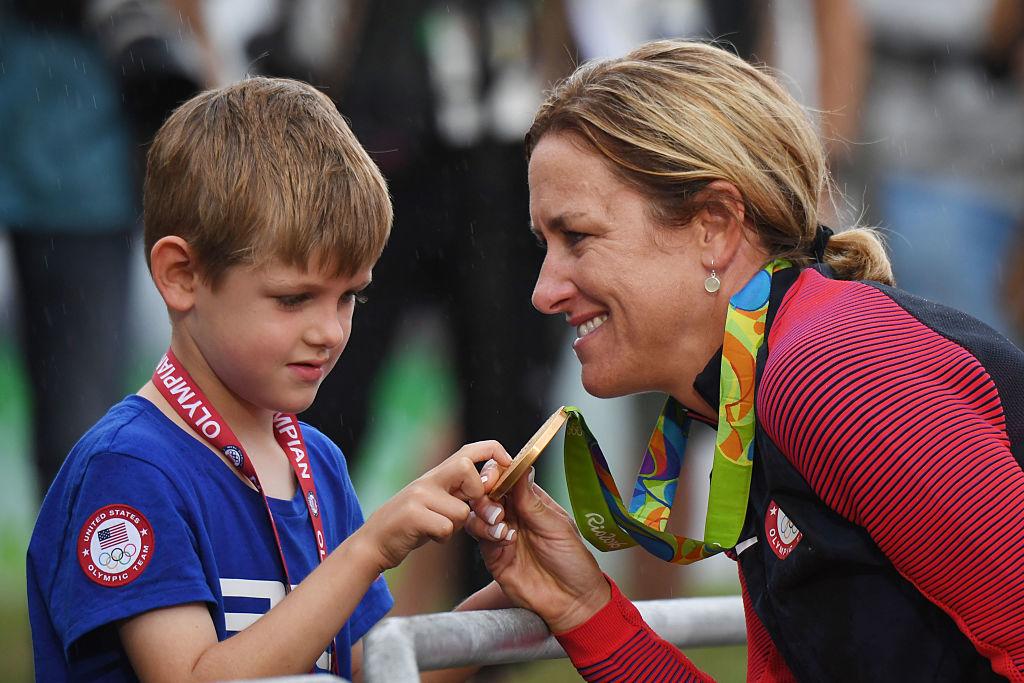 姬絲汀岩士唐贏得單車公路個人計時賽金牌後與兒子分享喜悅。(ERIC FEFERBERG/AFP/Getty Images)