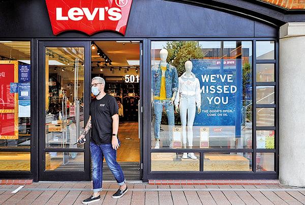 2020年6月16日,英國樸茨茅斯,一名Levi's服飾店員工戴著口罩。(ADRIAN DENNIS/AFP)