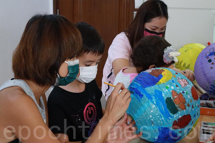 Michelle和兒子一齊畫燈籠。(陳仲明/大紀元)