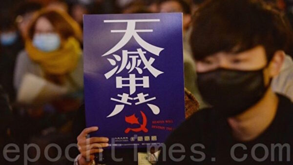 一名年輕的香港抗爭者,在抗議活動中手舉「天滅中共」的標語。(宋碧龍/大紀元)