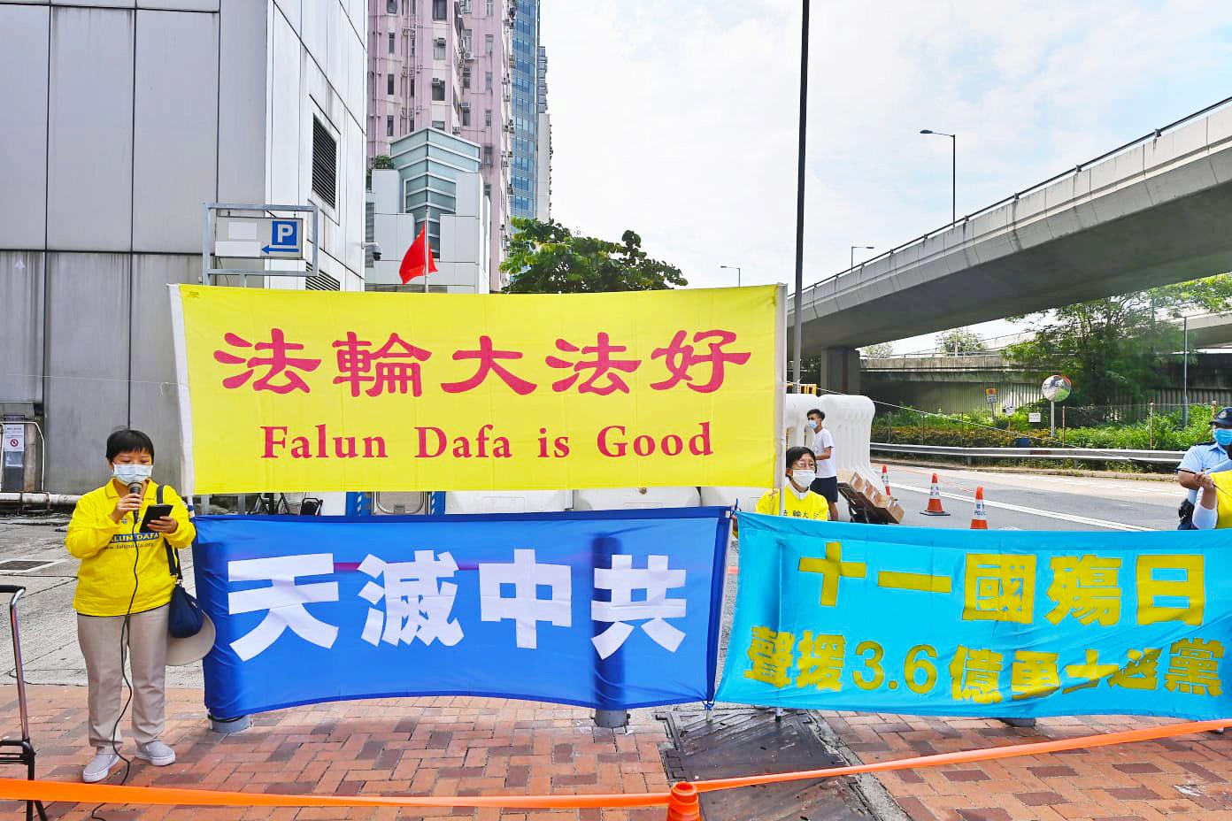 10月1日國殤日,香港法輪功學員在中聯辦門外舉起「法輪大法好」、「天滅中共」等標語。(宋碧龍/大紀元)