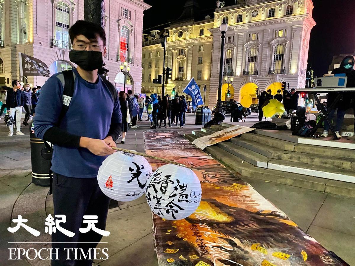 鄭文傑與寫有抗爭口號「光復香港 時代革命」的燈籠合照。(唐詩韻/大紀元)