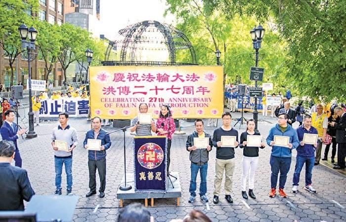 2019年5月16日法輪功學員紐約萬人集會上,全球退黨服務中心主席易蓉(左四)為8名來自中國大陸的華人公開「三退」並頒發「三退」證書。(大紀元資料圖片)