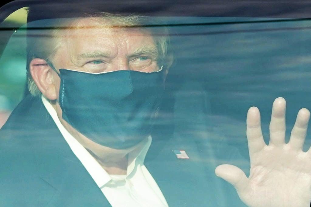 10月4日,因感染中共病毒在沃爾特里德(Walter Reed)國家軍事醫療中心治療的美國總統特朗普,短暫出院時在車中向沿途民眾揮手致謝。(ALEX EDELMAN/AFP)