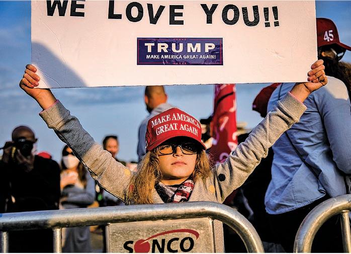 10月4日,美國馬里蘭州沃爾特里德國家軍事醫學中心外,一名女孩舉著「我們愛你」支持特朗普的標語,頭戴「讓美國再次偉大」的機車帽。(Samuel Corum/Getty Images)
