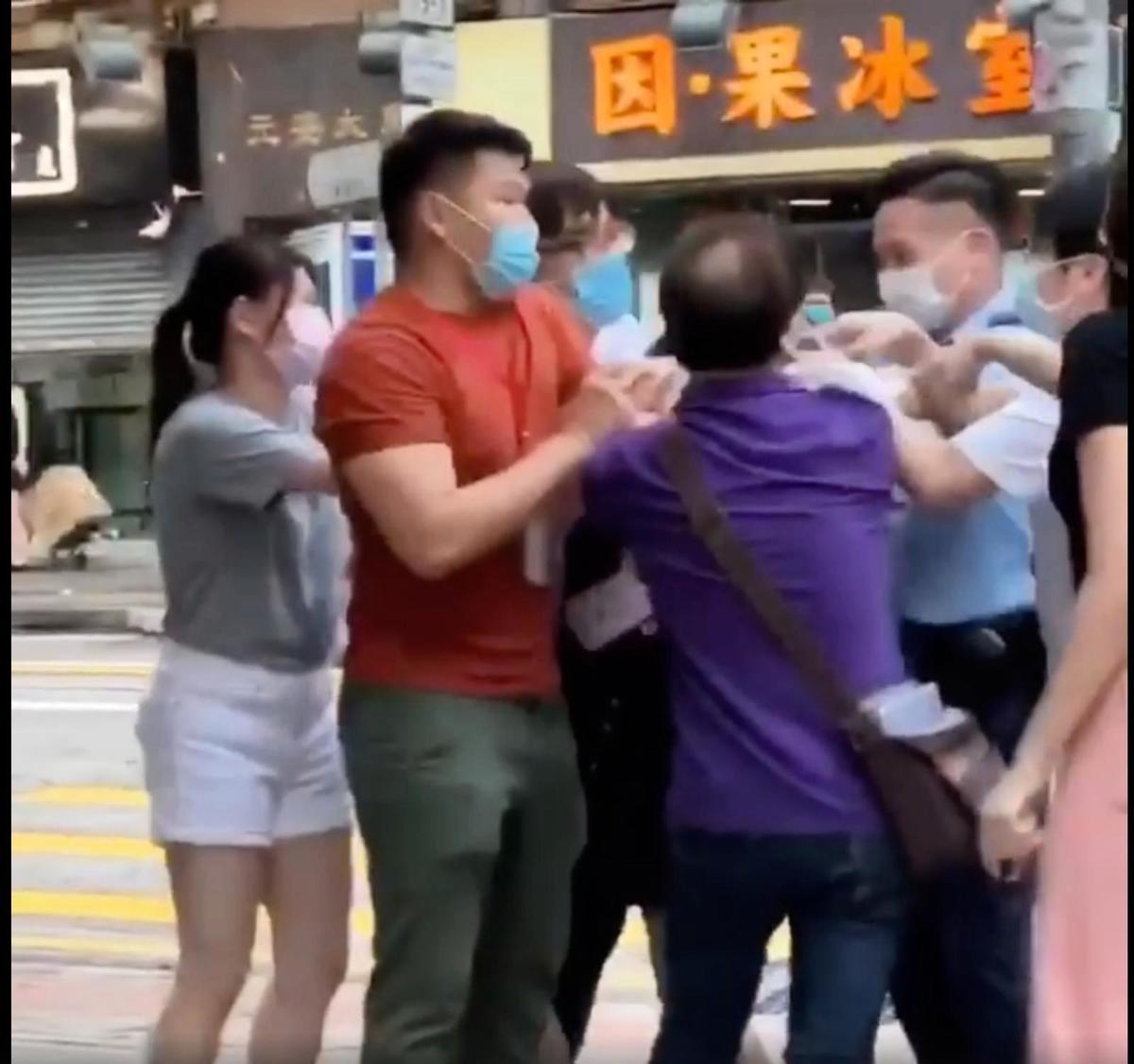今年5月29日,親共中年男子尹載道(紫色上衣)搗亂區議員反「香港國安法」街站,片段顯示他曾拉扯劉家衡區議員秘書白色上衣,最終卻雙雙被控在公眾地方打鬥。(南昌北 劉家衡 Facebook 影片截圖)