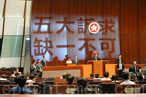 去年10月16日,林鄭宣讀施政報告期間,民主派立法會議員投射口號「五大訴求,缺一不可」抗議,最終林鄭拒絕繼續,改以視像形式發表。(大紀元資料圖片)