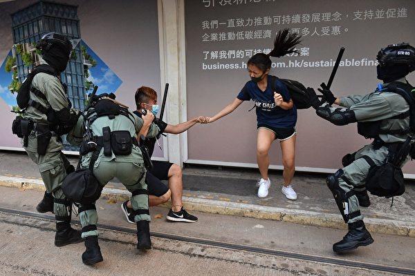2019年10月5日,香港警察在中環追捕一對戴口罩的年輕男女。(NICOLAS ASFOURI/AFP via Getty Images)