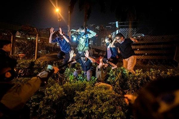 2019年11月19日,一群抗議者和學生在逃離香港理工大學後被警察逮捕。(NICOLAS ASFOURI/AFP via Getty Images)