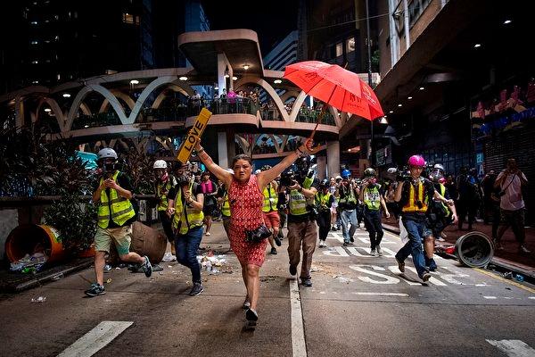 2019年10月1日,在香港銅鑼灣抗議現場的一名女子手持雨傘和標示有「愛」字的牌子。(NICOLAS ASFOURI/AFP via Getty Images)