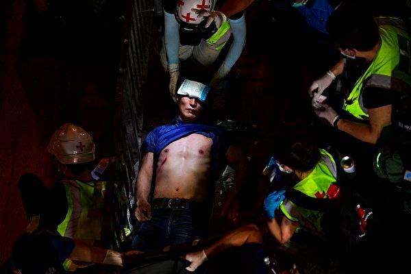 2019年9月15日,在香港地鐵北角站外,醫護人員在照顧一名受傷的男子。(NICOLAS ASFOURI/AFP via Getty Images)